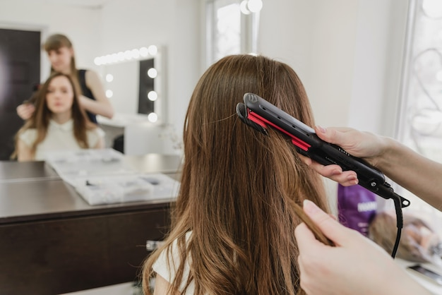 美容師は美容院で女の子のための髪型を作ります。アイロンで髪をまっすぐにします