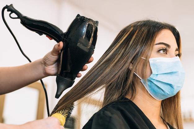 코로나 바이러스로 인해 얼굴 마스크에 아름다운 백인 소녀의 머리카락을 건조시키는 타격 건조기를 들고 미용사의 손. 소녀는 머리가 길다