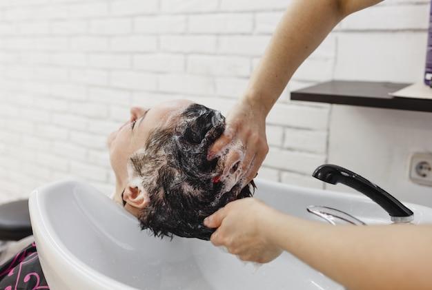 美容院のクローズアップで美容師がクライアントの頭をシャンプーする