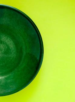 노란색 배경에 녹색 접시의 절반. 노란색과 녹색의 두 가지 주요 색상.