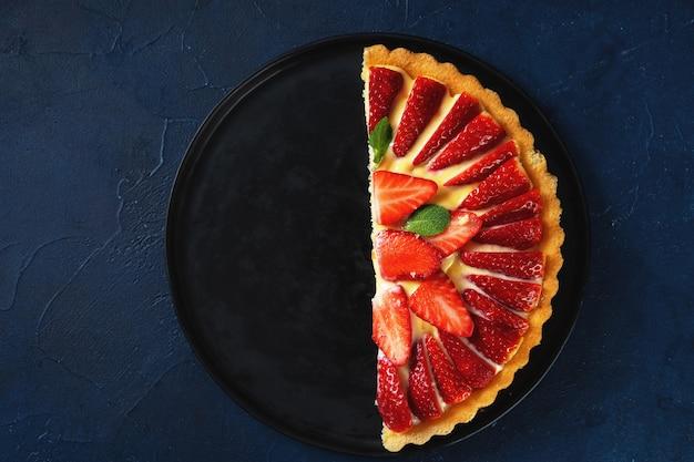 Половина свежего клубничного пирога на темном фоне