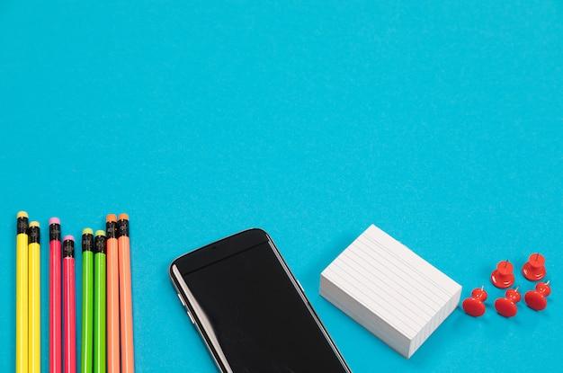 半分見えるカラフルな鉛筆、黒い携帯電話、白いスクラッチ紙のスタック、赤いピンのグループは、分離された淡いブルーの表面に横たわっています