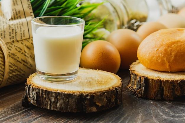 ハンバーガーパンと牛乳のガラスは、卵とスパイスの塩とコショウで木の幹のセクションにあります