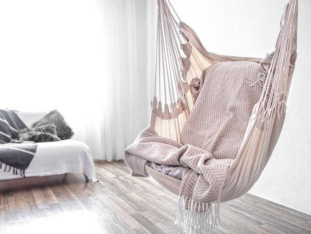 В комнате висит кресло-гамак. уютное место для отдыха дома.