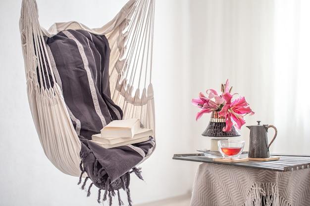 책과 찻 주전자와 차 한잔이있는 boho 스타일의 해먹 의자. 휴식과 가정의 편안함의 개념.