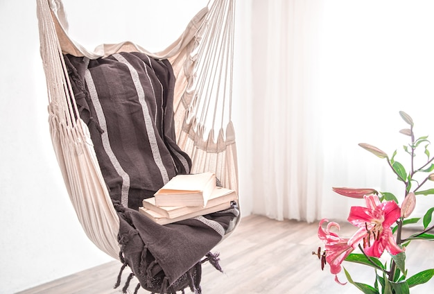 Кресло-гамак в стиле бохо со стопкой книг. концепция уютного места для отдыха дома.