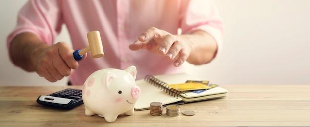 現金と木製の背景にコインで貯金箱を壊す手。
