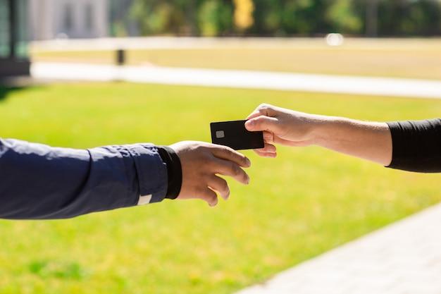 手は、銀行のクレジットプラスチックカードでクローズアップ。