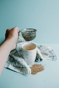 Рука держит дистиллятор чая над чашкой чая на пастельно-синем фоне