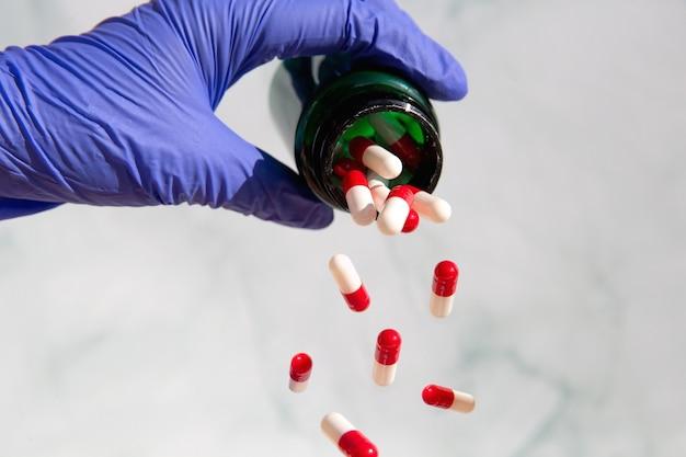 의약품으로 가득 찬 약국 항아리를 잡는 손, 비타민, 마약, 약이 떨어지는 캡슐. 건강, 비즈니스 개념 복사 공간 배경
