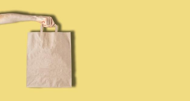 벽에 빈 단순한 종이 봉지를 들고 있는 손, 폐기물 제로 및 재활용 개념
