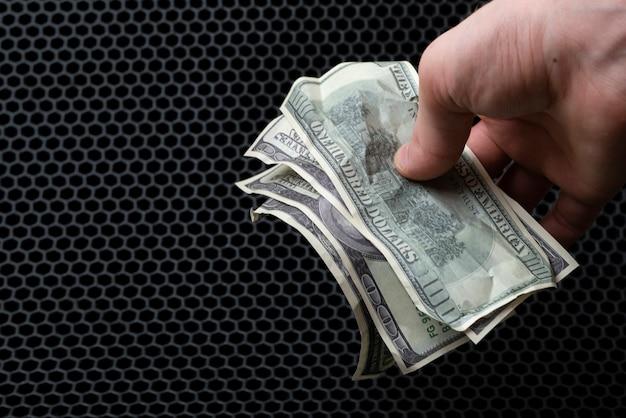 色の背景にドルの現金通貨を持っている手、シンプルな稼ぎのミニマルなコンセプト