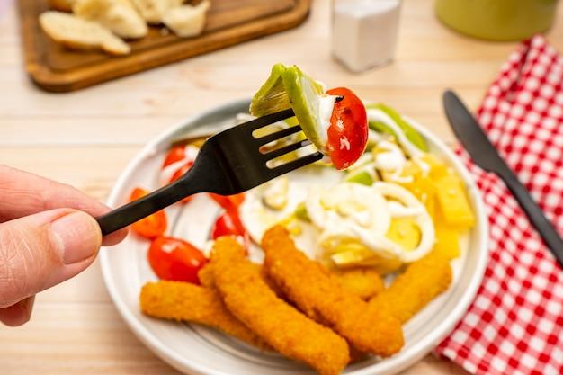 아보카도, 토마토, 아이올리 한 입과 맛있는 치킨 핑거와 신선한 샐러드가 있는 접시를 배경으로 포크를 들고 있는 손.