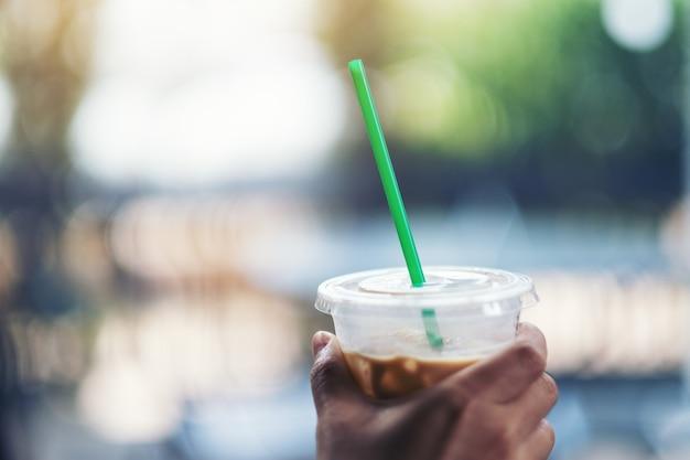 ストローでアイスコーヒーのプラスチックガラスを持っている手