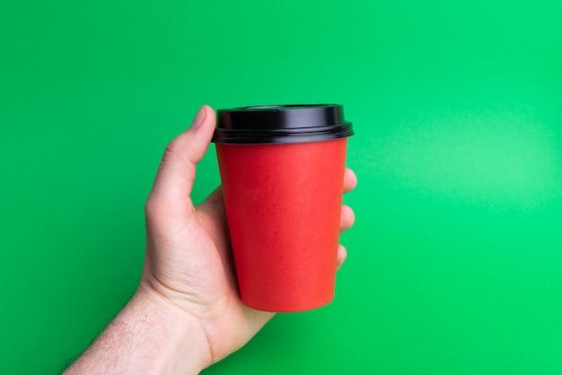 緑に赤のテイクアウェイカップを持っている手