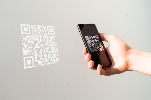 스마트 폰을 들고 qr 코드를 스캔하여 결제하는 손