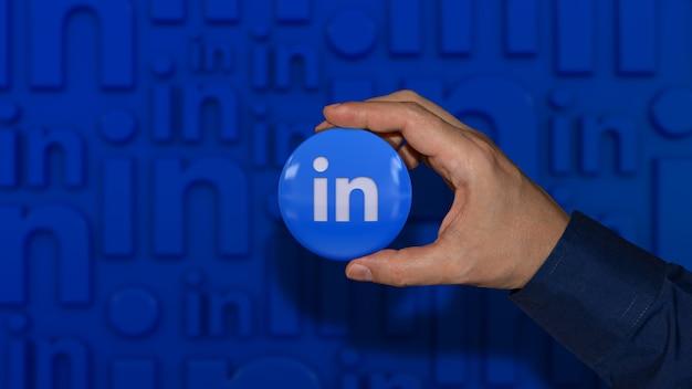Рука, держащая глянцевый значок с логотипом социальных сетей на синем несфокусированном фоне