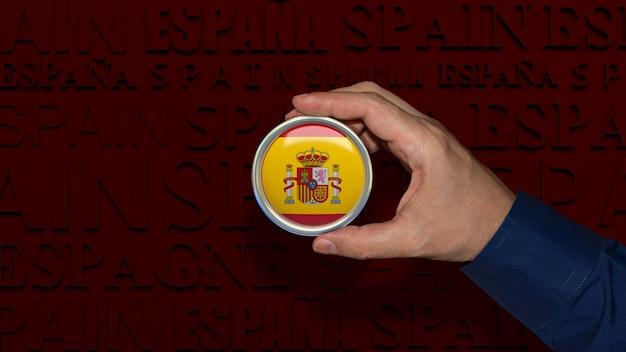 Рука, держащая значок испанского национального флага на темно-красном фоне