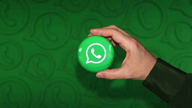 Рука, держащая глянцевый значок с логотипом whatsapp