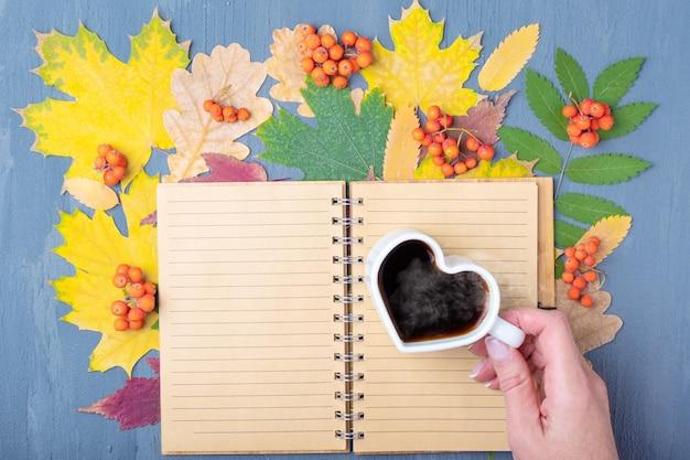 蒸しコーヒーまたは紅茶と秋の乾燥した色とりどりの葉の背景に空白の裏地付きクラフトメモ帳でハートの形をした白いマグカップを持っている手。秋の朝食。就業日計画