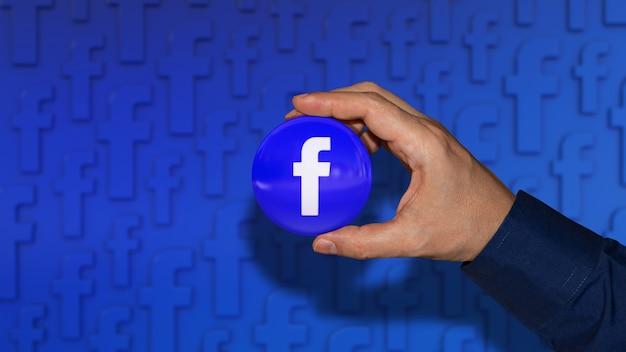 Рука, держащая глянцевый значок с логотипом facebook на синем Premium Фотографии