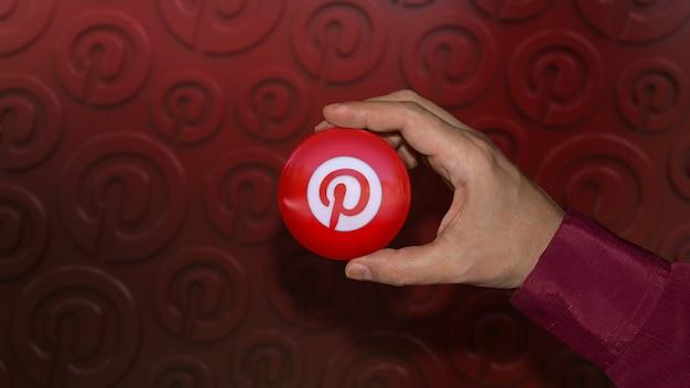 Рука держит глянцевый значок с логотипом pinterest на красном