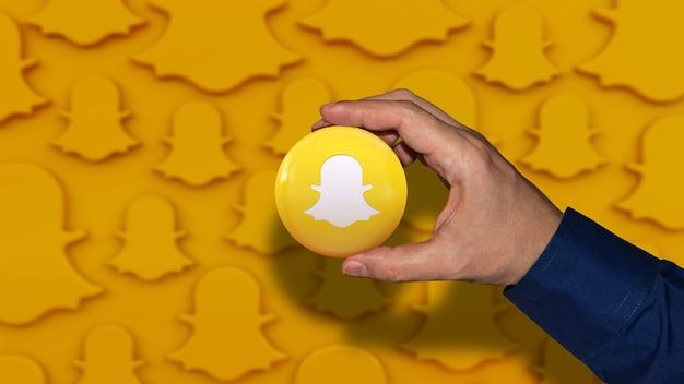 Рука, держащая глянцевый значок с логотипом snapchat на оранжевом