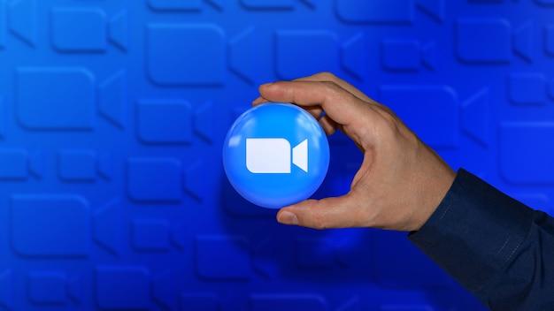 Рука, держащая глянцевый значок с масштабным логотипом на несфокусированном синем
