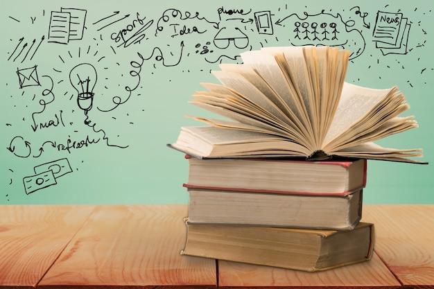 Рука, держащая книги со словами и буквами, представляющими концепцию образования и знаний