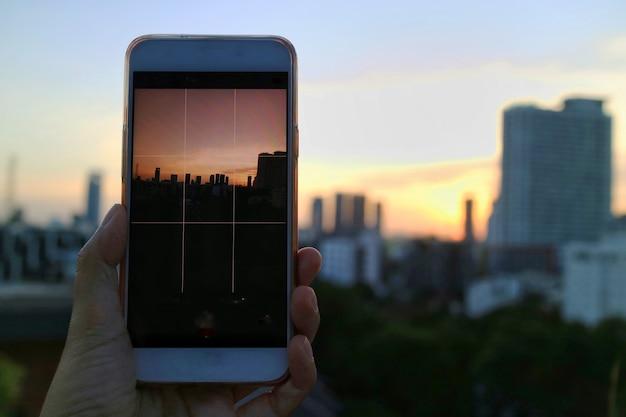 Рука мобильного телефона и принять фото закат рай с голубым небом