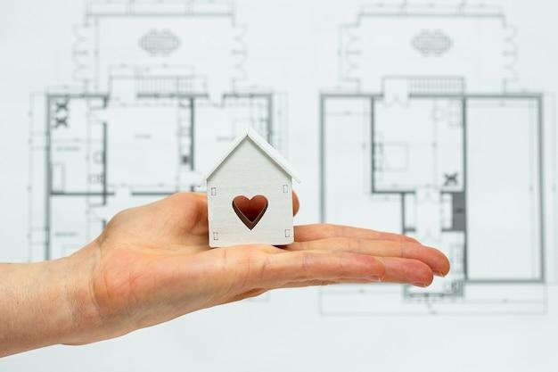 새 집 아이디어 또는 개념의 상징으로 장난감 집을 들고 손. 프리미엄 사진