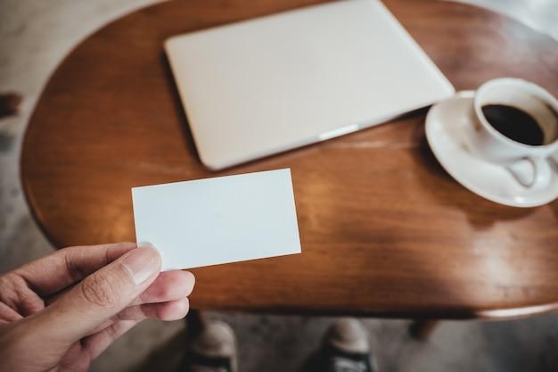 사무실에서 나무 테이블에 노트북과 커피 컵 흰색 빈 명함을 들고 손