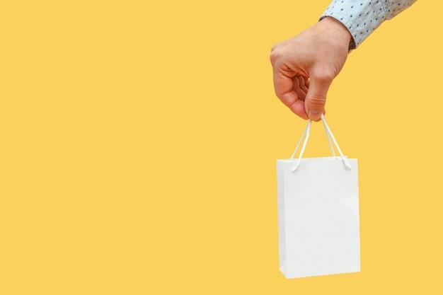 Рука держит подарок в белой сумке