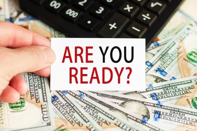 手には、紙幣と電卓がテーブルに刻まれた看板があります。金融と経済学の概念。