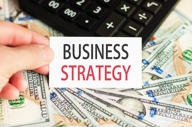 Рука держит табличку с надписью - бизнес-стратегия на стене банкнот и калькулятор на столе. концепция финансов и экономики.