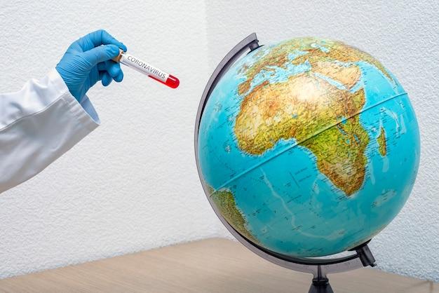 Рука держит пробирку с образцом ковид-19 рядом с планетой земля