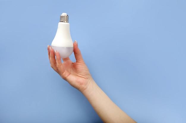 手は青い背景に白いled電球キャップを保持します。