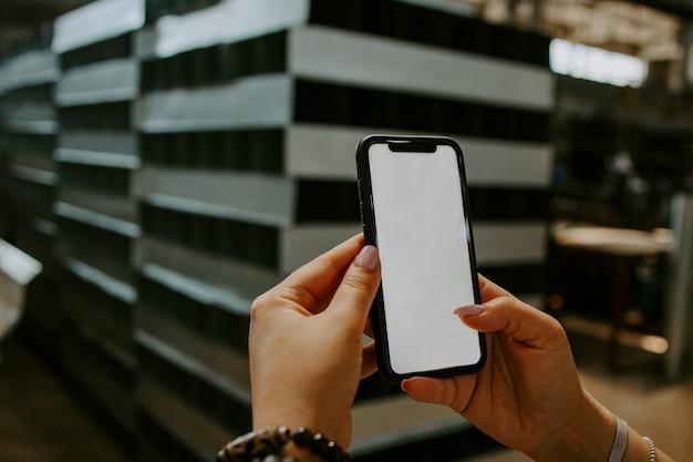 手は、工場の背景に空の白い画面で白い携帯電話を持っています