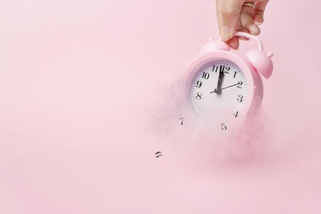 손은 알람 시계를 분해하고 입자로 분산시킵니다. 시간의 개념입니다. 라이트 핑크