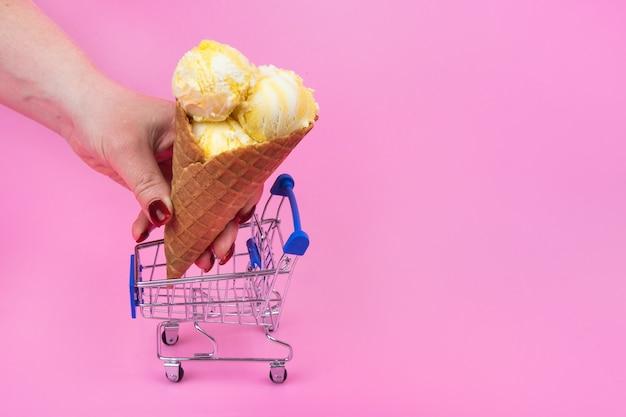 アイスクリーム コーンを手に持って買い物かごに入れる
