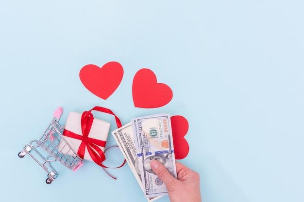 手はギフトボックスと赤い愛の心を持つショッピングカートの上に現金ドルを保持します