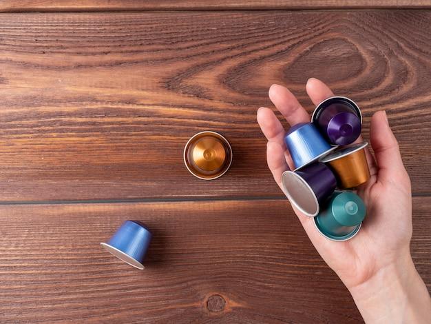 手は茶色の木製の背景の上にコーヒーマシン用の色付きのアルミニウムコーヒーカプセルを保持します。コーヒーを保存および製造するための最新のソリューションの概念