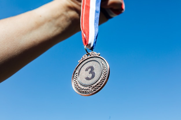 空を背景に、手が3位の銅メダルを掲げています。勝利の概念