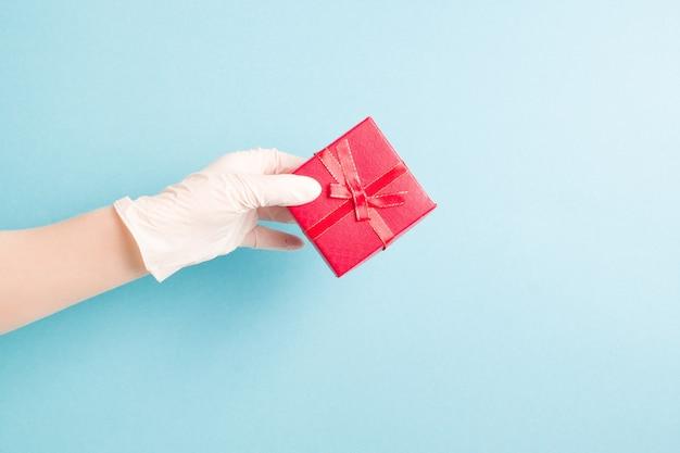 Рука в синей одноразовой перчатке держит красный свет подарочной коробки, синий фон, копировальное пространство