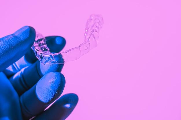 青い手袋をはめた手でアライナーを握り、歯を矯正します。プラスチック製のブレース歯科用リテーナーで歯を矯正します。
