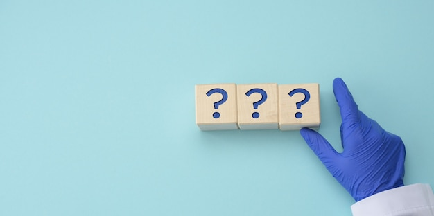 青い医療用手袋の手は、青い表面に疑問符の付いた立方体を持っています。未知の、なぞなぞ、未回答の質問、コピースペースの概念