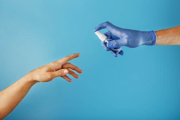 소독 스프레이가있는 장갑을 낀 손은 보호되지 않은 손을 치료합니다.