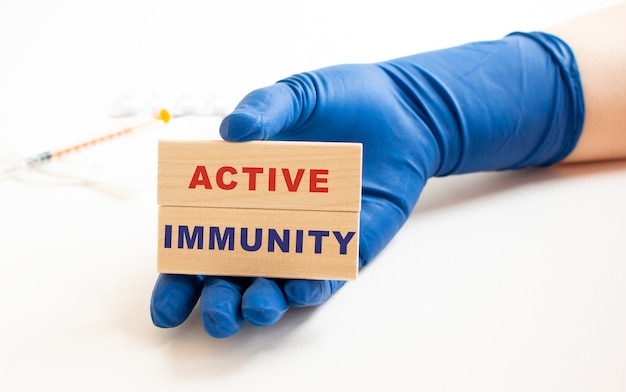 의료용 장갑에 든 손에는 active immunity라는 문구가있는 나무 큐브가 들어 있습니다. 의료 개념.