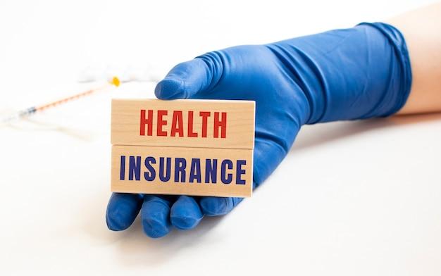 의료 장갑에있는 손에는 건강 보험이라는 비문이있는 나무 큐브가 들어 있습니다.
