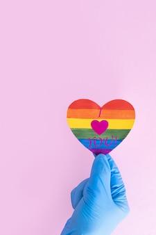 Рука в медицинской защитной перчатке держит форму сердечка из бумаги радуги с надписью i love you на розовом фоне, вертикальной рамкой, копией пространства. концепция безопасной любви. концепция лгбт